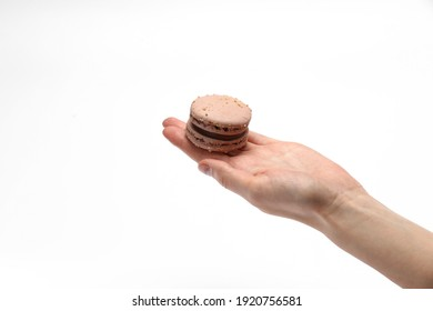 hand holding sweet and colourful french chocolate macaroons or macaron isolated on white background
