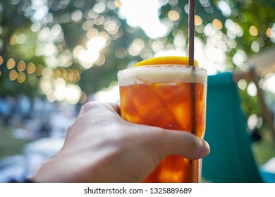 Hand holding sweet Lemon Iced Tea in relaxing day at beach or laying by the pool taking sips cold drink. A summer favorite beverage with refreshing and full of fruity flavor