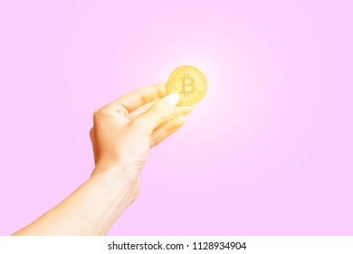 Hand holding symbol of cryptocurrency - gold bitcoin on a pink background.