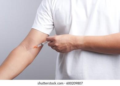 Hand holding syringe as drug patient on white background