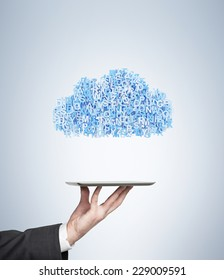 A hand holding a tablet with flying social networking icons in a cloud. Blue background.