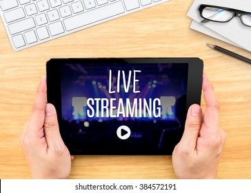Hand holding tablet with Live Streaming word on wood table ,Internet marketing concept.
