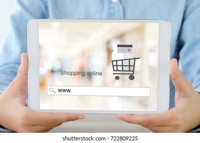 Hand holding tablet with www. on search bar over blur store background on screen, on line shopping , business and technology, E-commerce, digital marketing concept