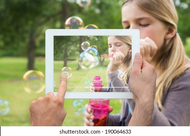 Hand holding tablet pc showing little girl blowing bubbles in the park