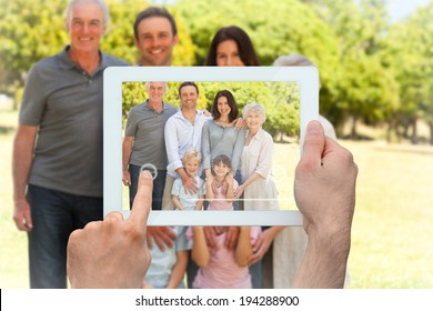 Hand holding tablet pc showing family standing in the park