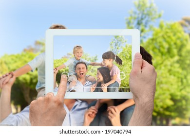 Hand holding tablet pc showing parents giving children a piggyback