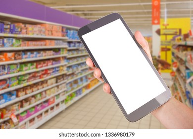 Hand holding tablet smartphone in shopping mall corridor next to good shelf. White screen mock up conceptual image with copy space for your own creativity