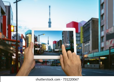 Hand holding tablet use AR application to check relevant information. Japan City in marketing street background concept.