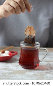 hand holding tea bag, dipping a tea bag