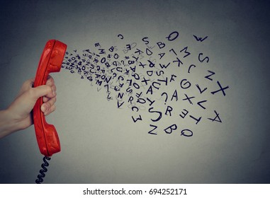 Hand holding telephone handset with alphabet letters coming out. Too many words during conversation concept