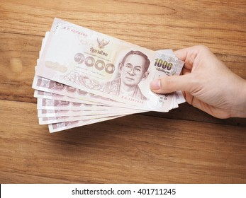 Hand holding Thailand banknote, kind of thousand Thai baht,  in giving position, wood background.