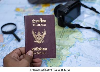 Hand holding Thailand passport