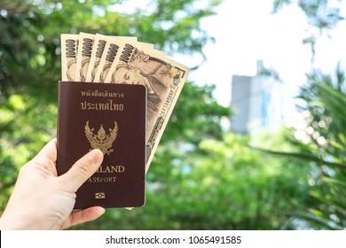 "hand holding thailand passport and japanese money with fresh green background, thai text means ""Thailand passport"""