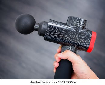 Hand holding a therapeutic percussive massage gun isolated against a dark background with copy space