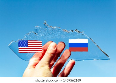 hand holding a thin transparent piece of ice in the shape of an Arctic iceberg with the flag of the USA and Russia against a blue sky. The concept of the struggle for Arctic. Arctic shelf, Cold War