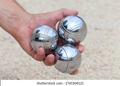 Hand is holding three Bocca balls to play Jeu de Boule, a typical French game