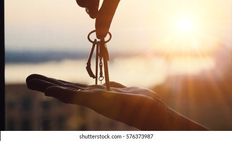 Hand holding three keys over the hand on sunset background, Building concept