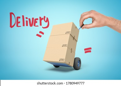 Hand holding tiny hand truck with cardboard boxes and 'Delivery' sign on blue background. People and objects. Transportation and delivery. Digital art.