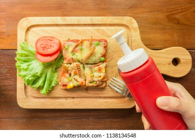 Hand holding a tomato sauce bottle to eating woodworm, edible insects. on a wooden cutting board. Closeup, Selective focus, Top view