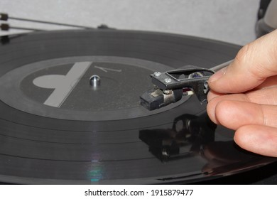 Hand holding tonearm shell over a record