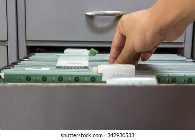 Hand holding top secret file in filing cabinet