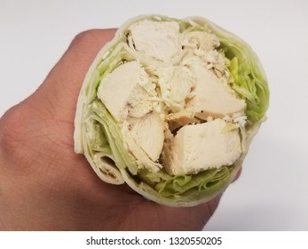 hand holding tortilla wrap with chicken and lettuce