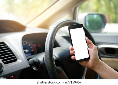 Hand is holding a touch phone with isolated screen in the car.