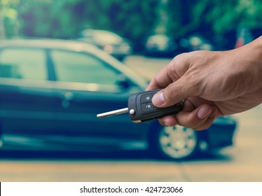 Hand holding and touching the keys over photo blurred of used car for open the door car, transportation and ownership concept, car key concept