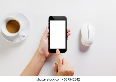 Hand Holding and Touching Modern Black Color Smartphone On White Table Workspace And Clipping Path Inside On Screen