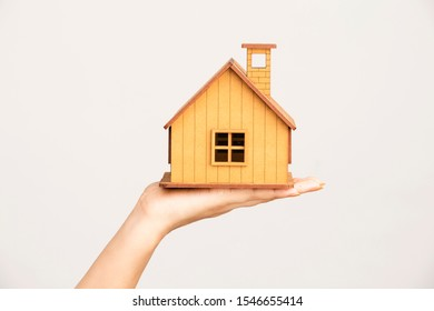 Hand holding toy house ( Real estate concept )