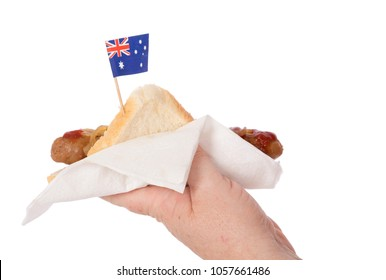 A hand holding a traditional Australian Sausage Sizzle.