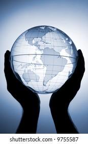 Hand holding translucent globe with blue background