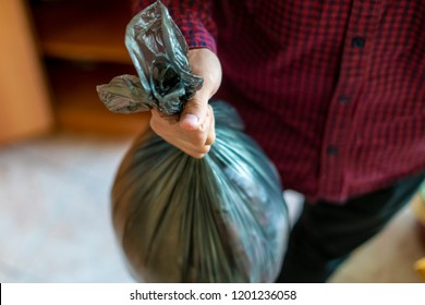 hand holding a trash garbage bag at home to take it away