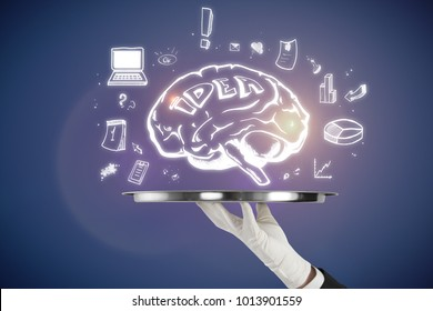 Hand holding tray with brain sketch on blue background. Brainstorming and marketing concept