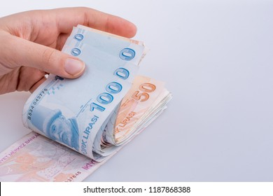 Hand holding Turksh Lira banknotes  on white background
