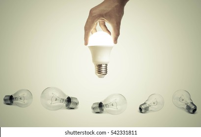 Hand holding a turned on LED light bulb over old incandescent light bulbs / Using economical and environmentally friendly light bulb concept