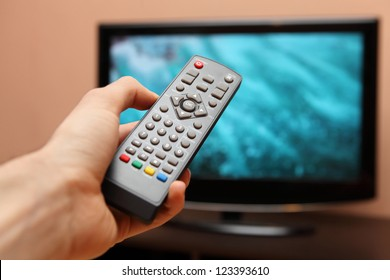 Hand holding TV remote control with a television in the background