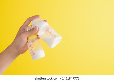 Hand holding two baby bottle of milk on yellow background