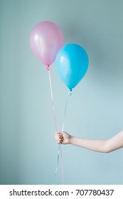 hand holding two balloons
