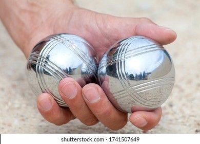 Hand is holding two Bocca balls to play Jeu de Boule, a typical French game