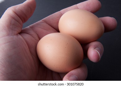 A hand holding two brown eggs.