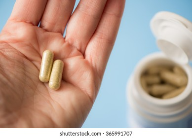 Hand holding two capsules and opened medicine bottle in the background