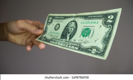 Hand holding two dollar bill. The United States two-dollar bill ($2) is a current denomination of U.S. currency. A portrait of Thomas Jefferson.