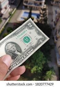 Hand holding two dollars bill in front of the sunny lush foliage landscape. Money saving for travel concept.