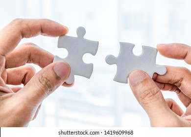 Hand holding two pieces of jigsaw connecting couple puzzle.Fulfill and  fix the problem of incomplete.Business solutions for success and strategy concept.