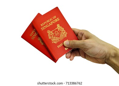 Hand holding two Singapore Passport isolated on white background, selective focus. Clipping path included.