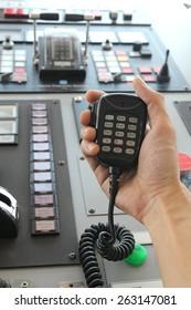 Hand holding two way radio receiver on bridge of ship