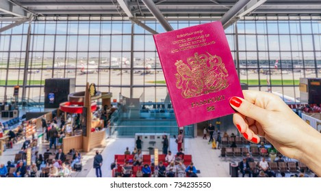 Hand holding UK passport with busy airport waiting lounge and airplanes in background