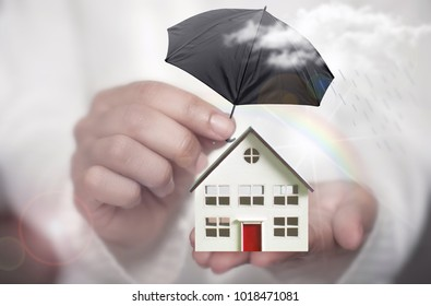 Hand holding umbrella protecting a house from rain