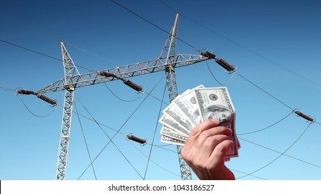 Hand holding US dollar bills in front of a high voltage power lines